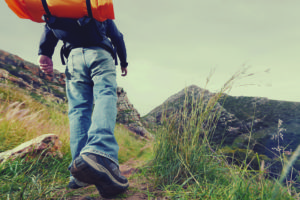 Adventure man hiking wilderness mountain with backpack, outdoor