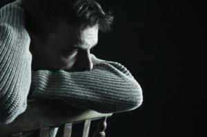 Sad depressed man sitting in the dark. Feelings of grief or loss